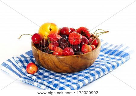 Gooseberries, strawberries, cherries, peaches are in a wooden bowl. on a blue checkered napkin. White background.