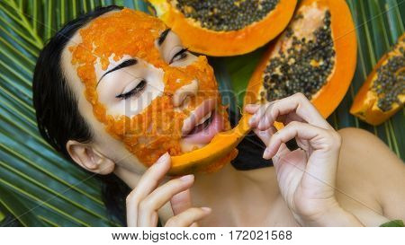 Beautiful caucasian Woman Having fresh Papaya natural facial mask apply. Papaya Peeling. Skin care and Wellness (outdoors). Facial vitamin mask of papaya slices at spa salon. Antioxidant cosmetic poster