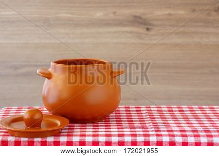 Empty ceramic pot on a checkered tablecloth. Next is the cover. Wooden background