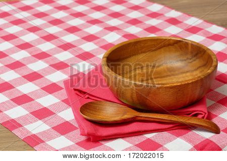 Empty wooden bowl and spoon on a red checkered tablecloth.  Rustic style. Free space for creativity.