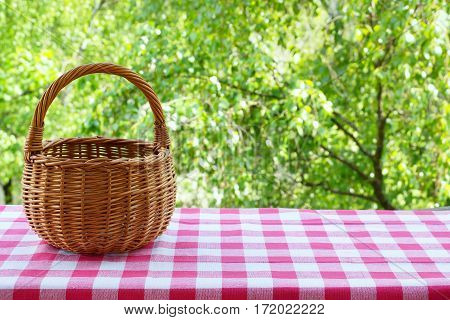 Empty basket on the table with checkered table cloth on a background of green trees.  Free space for creativity.
