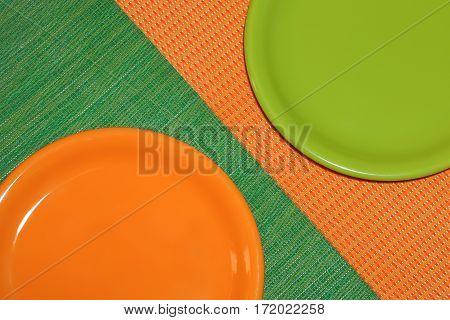 Two empty plates arranged diagonally. Orange on a green napkin, green on orange napkin. Top view