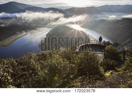 Tourist looks at Alagon River Meander with sunrise in the morning alone and active lifestyle. This place is called The Melero and is not far from Riomalo de Abajo Hurdes Spain