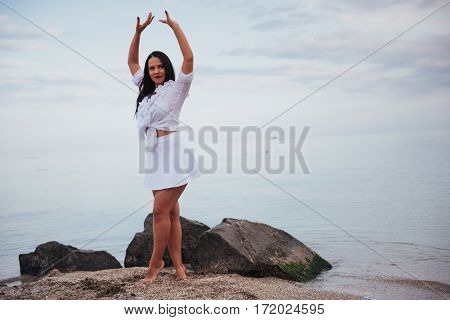 woman in a white shirt and skirt dancing barefoot on the sand beach hand above the azure sea breeze shakes her long hair