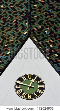 Close up of Church tower with colorful roof tiles and Clock