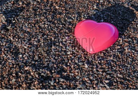 Red plastic heart lies on the sand. pea gravel.