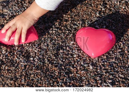 Red Plastic Heart Lies On The Sand. Pea Gravel