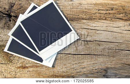 Old blank photos on the rustic wooden background