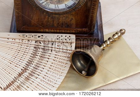 Still Life, Brass Bell, Antique Clock And Carved Wooden Fan