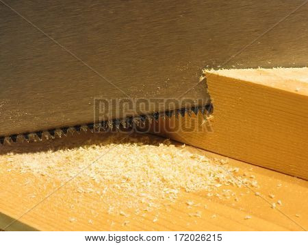 Close up of a hand saw cutting a piece of wood on a wooden workbench