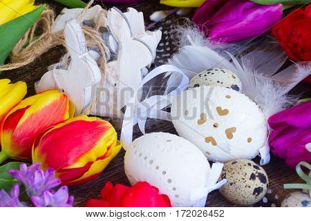 Spring fresh flowers with easter eggs and white wooden rabbits close up