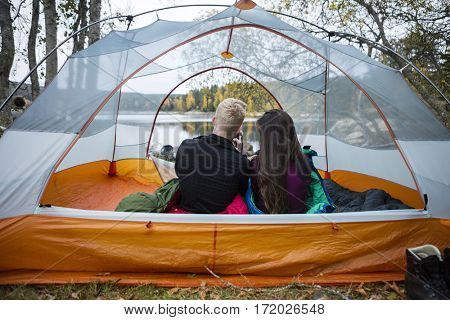 Young Couple Enjoying Lake View From Tent