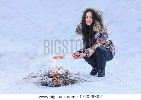 Outdoors Winter Barbecue . Woman Cooking Sausages Over Hot Coals