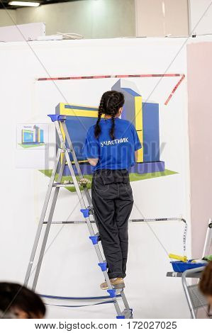 Tyumen Russia - February 17. 2017: Open championship of professional skill among youth World skills Russia Tyumen - 2017. The girl painter decorates a wall performing a task