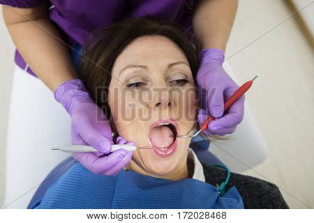 Patient With Mouth Open Being Examined By Dentist Holding Tools