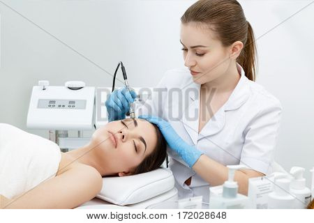 Procedure of Microdermabrasion. Mechanical Exfoliation, diamond polishing. Model and doctor. Cosmetological clinic. Healthcare, clinic cosmetology poster