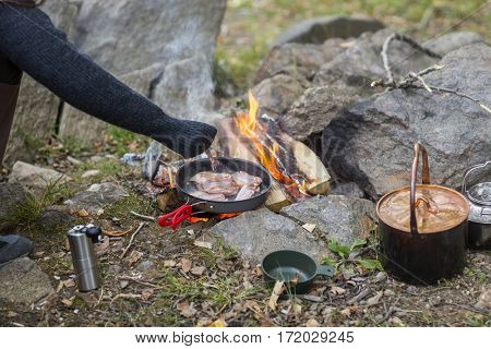 Woman Cooking Food Over Bonfire At Campsite