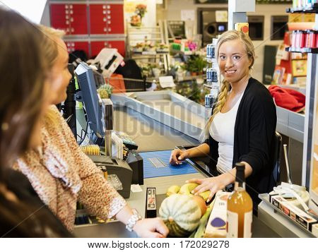 Cashier Smiling While Customers Standing At Checkout Counter