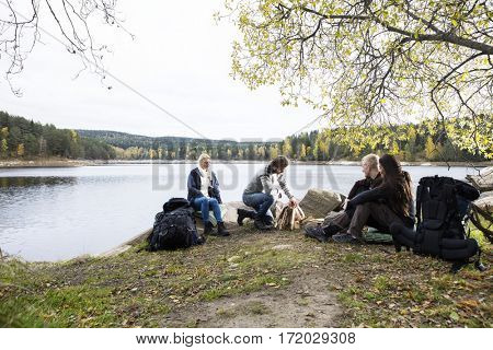 Friends Looking At Man Preparing Bonfire On Lakeside Camping