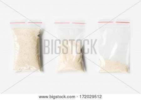 Set Of Three Empty, Half And Full Plastic Transparent Zipper Bag With Dry Raw Wheat Semolina Isolate