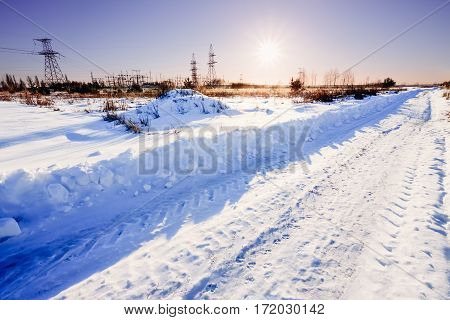 Sunset in the winter on the Russian rural road with snowdrifts, near the power station