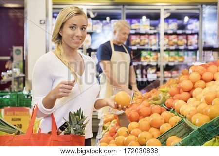 Female Customer Holding Orange In Grocery Store