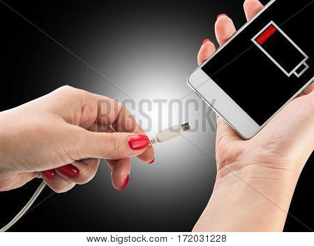 Female hand holding low battery smartphone and connect charger isolated on black background