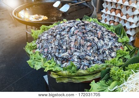 many raw mussel prepare for cook is mussel pancakes or Oyster omelette (Hoi Tod) in local street food market Thailand