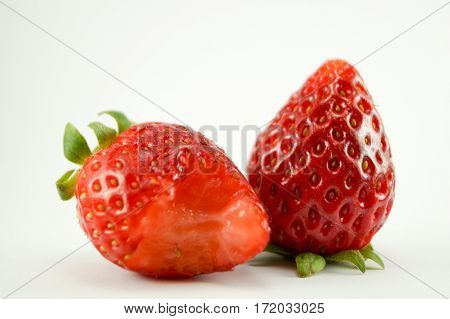2 Strawberries have white background.One strawerry is eaten.You can see it closeup with macro.