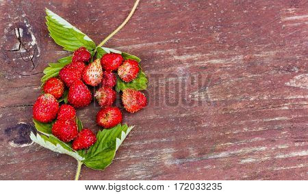 Strawberry With Green Leaves On Wooden Table