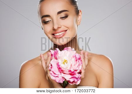 Beauty portrait of model with big pink flower. Woman holding flower with both hands. Head and shoulders, looking down and smiling. Studio, indoors, gray background