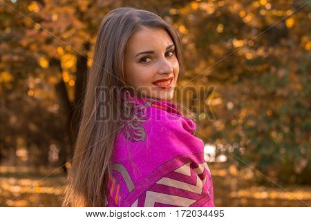 girl stands sideways in a big warm scarf on the shoulders and smiles