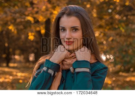 girl stands up straight and looking forward the hands behind scarves close-up