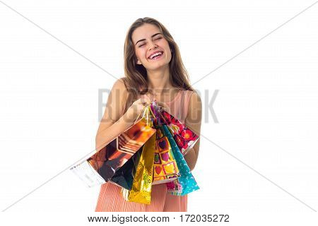 fun pretty girl closing her eyes keeps packages from stores isolated on white