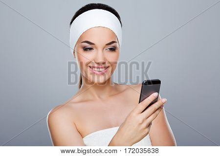 Woman with white headband holding phone. Model looking at phone and smiling. Head and shoulders. Beauty salon, studio, indoors, grey background