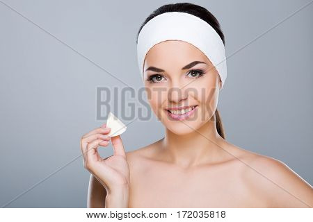 Woman with white headband holding white sponge. Model looking at camera and smiling. Head and shoulders. Beauty salon, studio, indoors, grey background