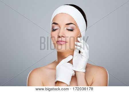 Woman with white headband touching face and neck with hands in white gloves. Model with closed eyes. Head and shoulders. Beauty salon, studio, indoors, grey background
