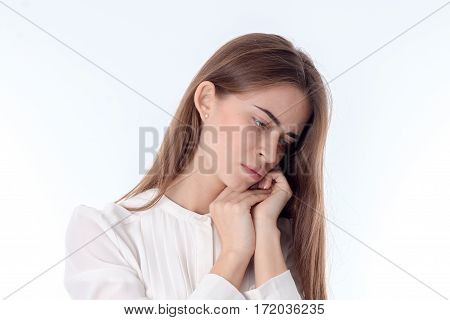 young girl tilted her head down and keeps hands near individuals is isolated on a white