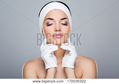 Woman with white headband touching chin with both hands in white gloves. Model with closed eyes. Head and shoulders. Beauty salon, studio, indoors, grey background
