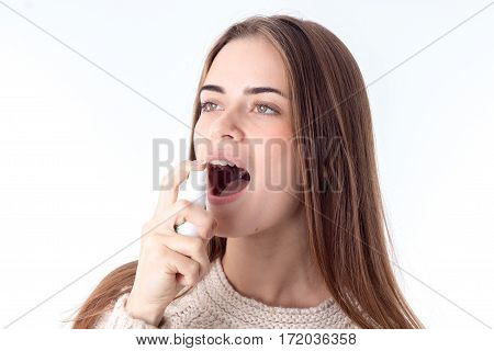young girl squirting sore throat spray is isolated on a white