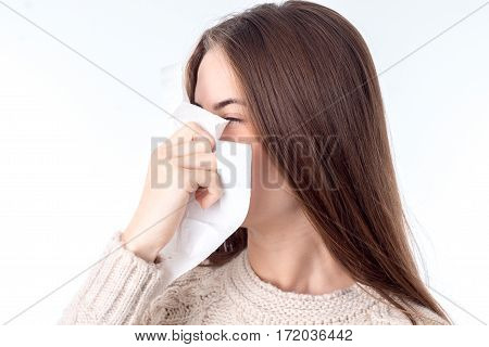 young girl with sniffles wipes nose isolated on white