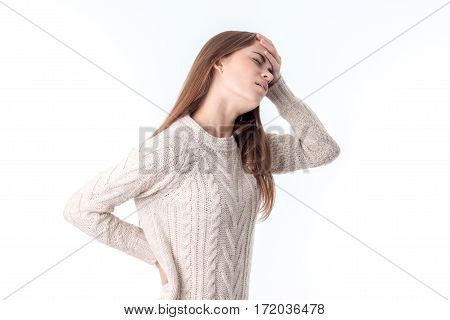 a girl in a sweater stands sideways put one hand on the side and the second hand is held behind the head isolated on white