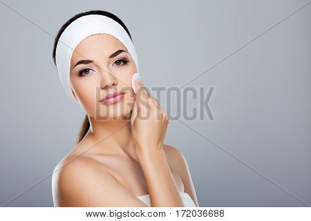 Woman with white headband touching her face with cotton pad. Model looking at camera, head and shoulders. Beauty salon, studio, indoors, grey background