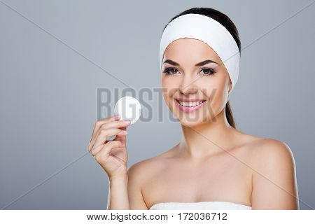 Woman with white headband holding cotton pad. Model looking at camera and smiling, head and shoulders. Beauty salon, studio, indoors, grey background