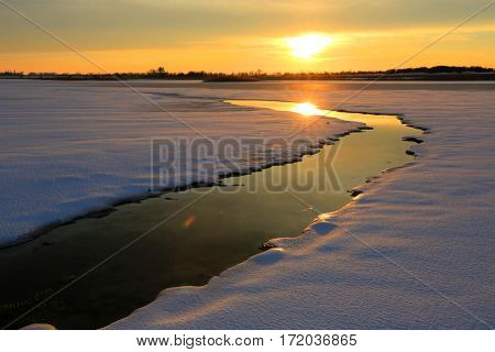 winter sunset scene on small river in steppe