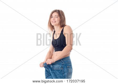 a cheerful young girl wore large trousers and laughs is isolated on a white