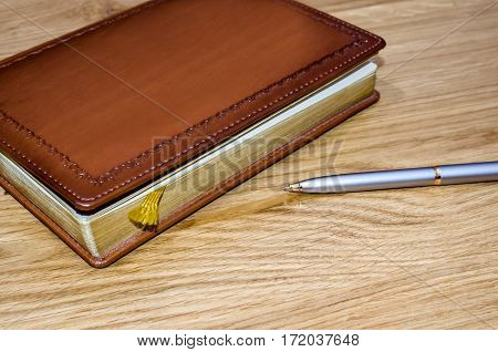 closed old brown leather notebook and fountain pen on wooden boards