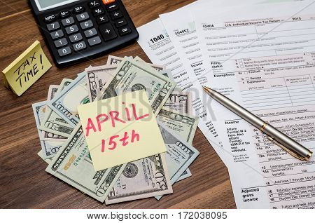 1040 Tax Form With Sticky Note Of April 15, Us Dollar  And Calculator