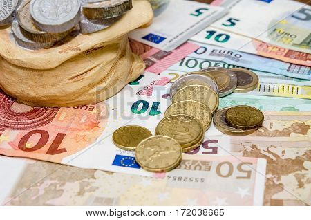 Piggybank coins and euro bills close up
