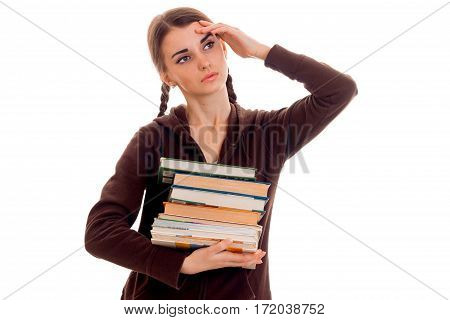 tired student girl in brown sport clothes with a lot of books in her one hand and second on her head posing isolated on white